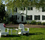 Two white Adirondack chairs in the grass with Captain's House Inn in the background