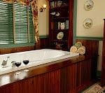 Deep bath tub trimmed in wood with two wine glasses