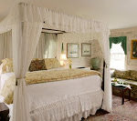 Beautiful spacious guest room with several windows and four poster bed with white canopy