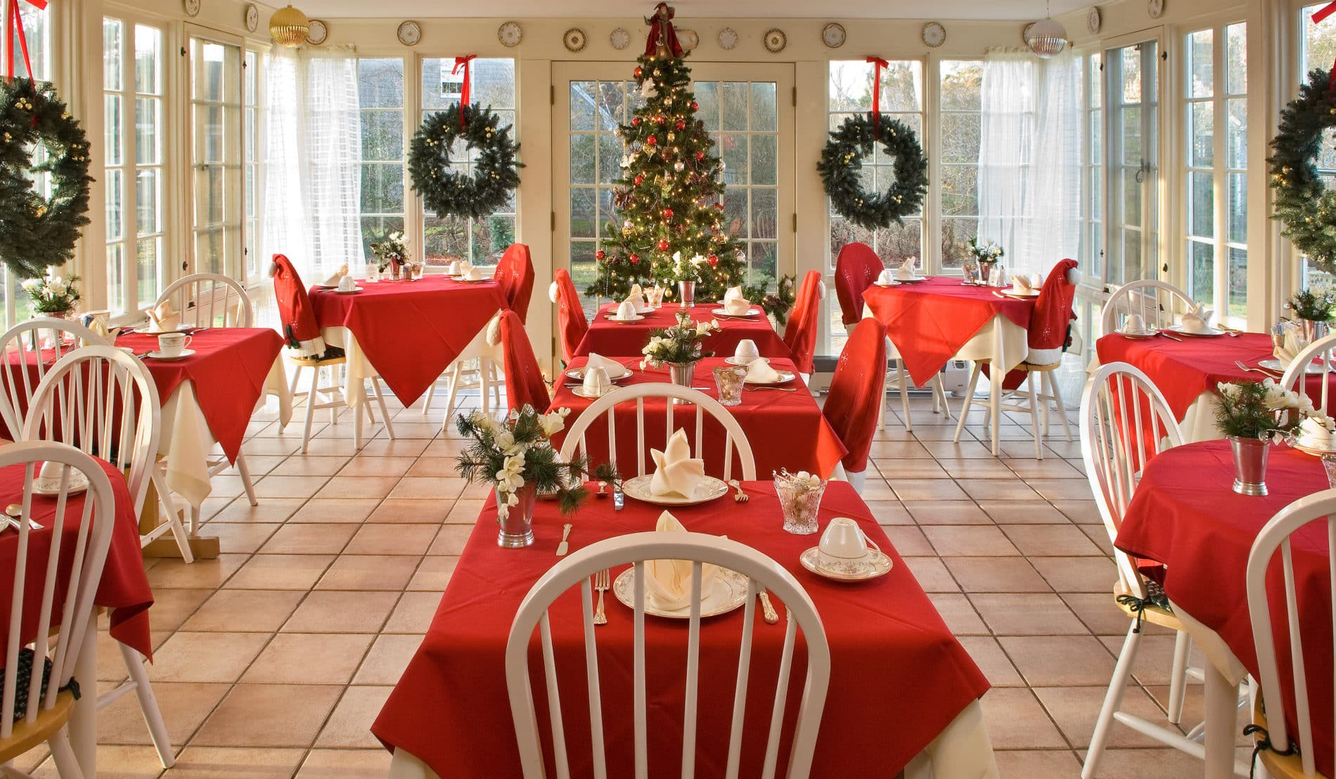 Spacious room surrounded by windows with several white dining tables draped in red cloths set for a meal at Christmas