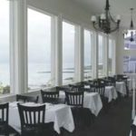 Restaurant with white draped tables in front of a wall of picture windows overlooking the water