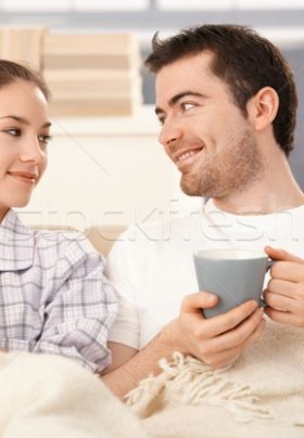 Man and woman sitting in bed in their PJ's holding coffee cups