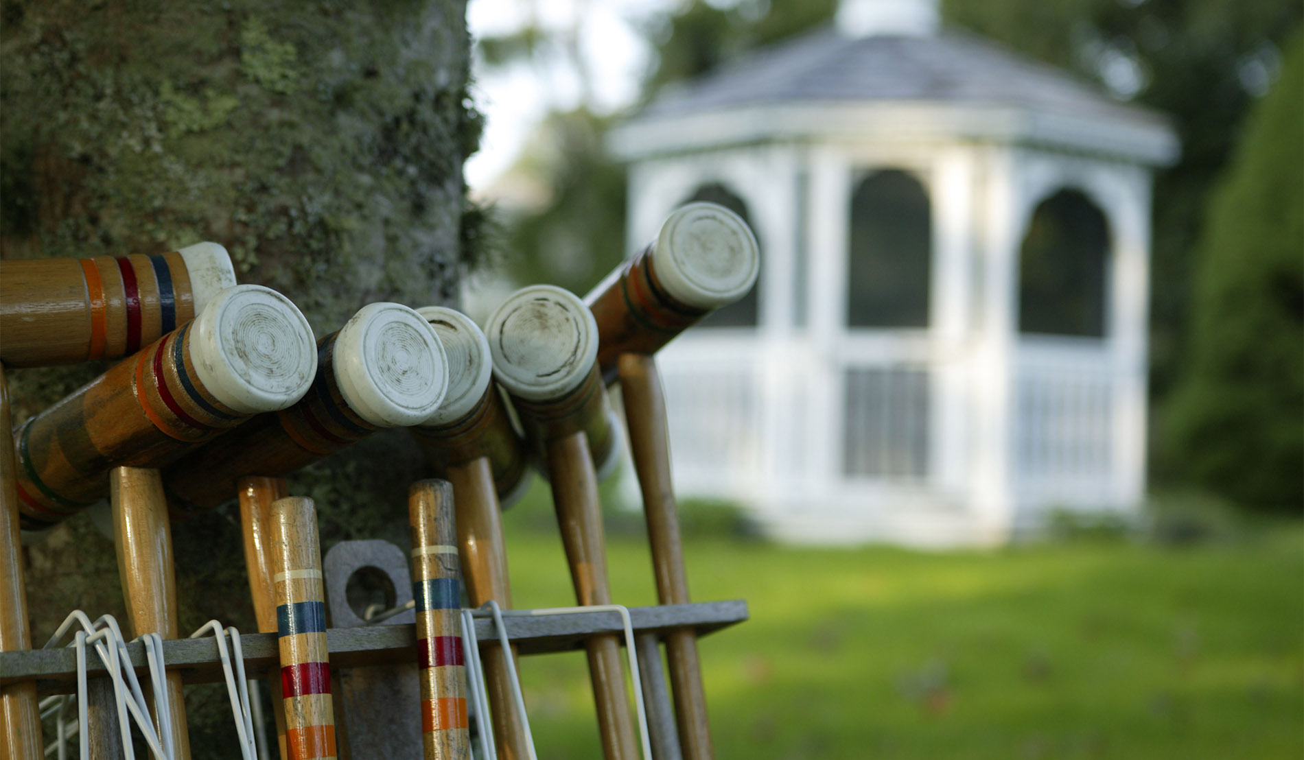 White gazebo on front lawn of Captains House Inn with croquet equipment