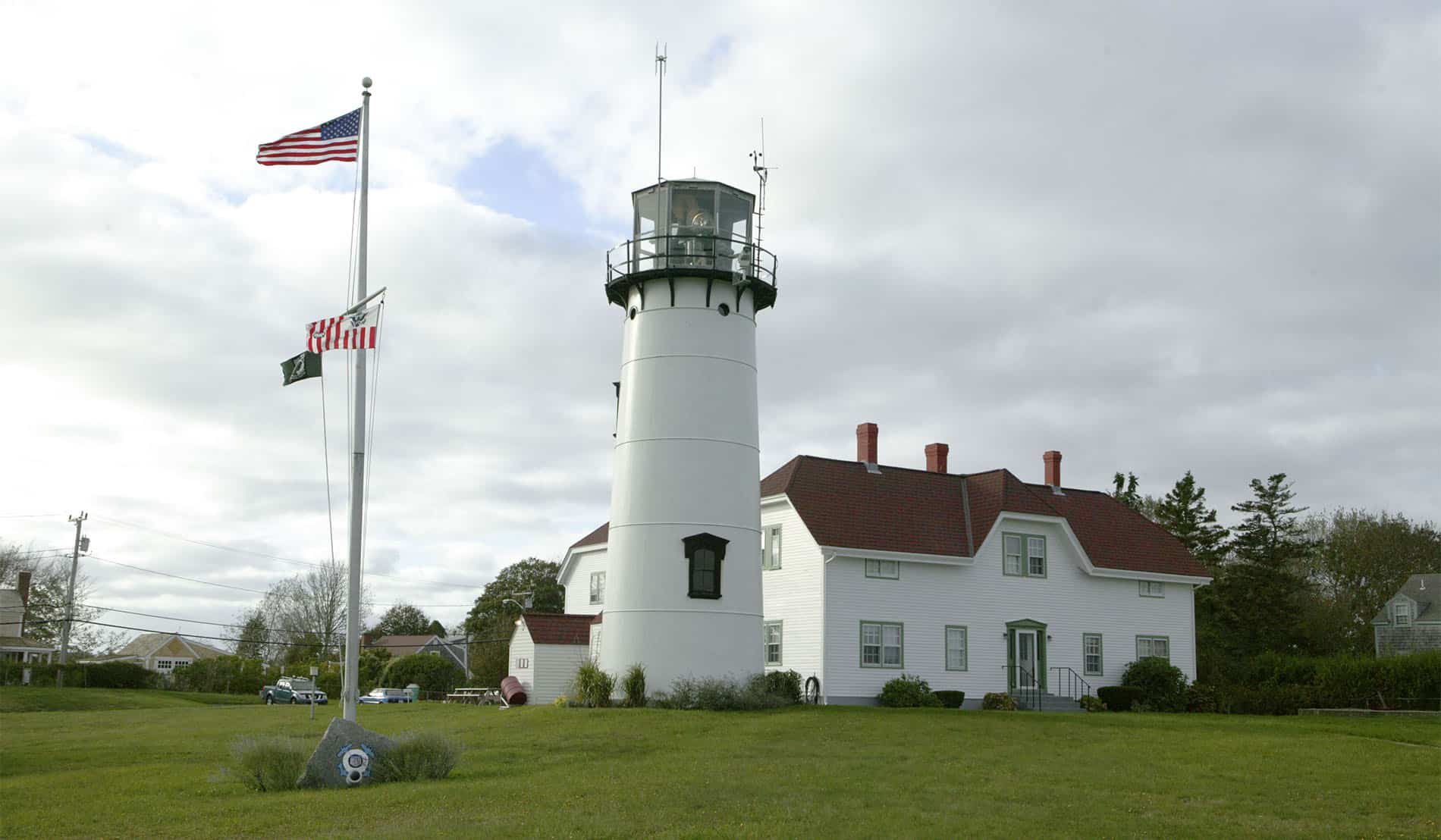Chatham Lighthouse with sprawling green lawn and American flag in front