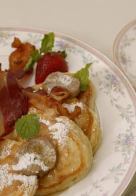 White plate trimmed in pale flowers topped with apple pancakes, powdered sugar, crispy bacon, strawberries and syrup