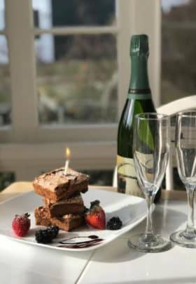 White plate topped with brownie stack cake a lit candle and fresh berries next to Champagne bottle and two glass flutes