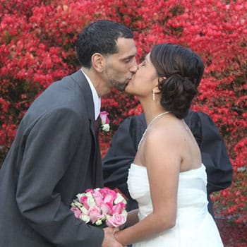 Bride and groom kissing in front of a bright pink flowering tree