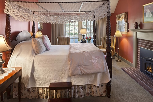 Cape Lady guest room showing rose painted walls and queen canopy bed
