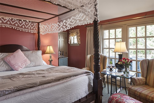 Cape Lady guest room with large window, four poster canopy bed with lace canopy and wingback chairs
