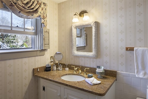 Cape Lady guest bath with papered walls, window, vanity, mirror and sconce light