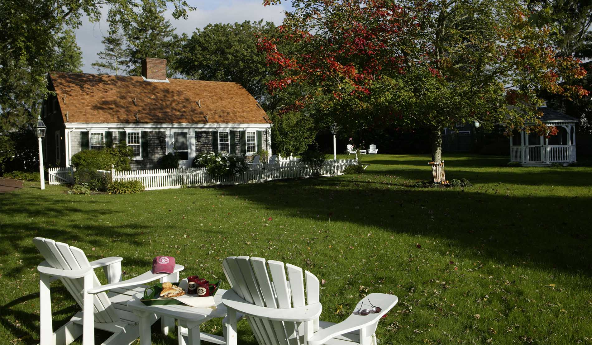 Exterior view of Captains Cottage with white Adirondack chairs and gazebo