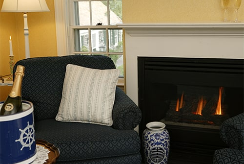 Clarissa Suite living room showing gas fireplace and blue cushioned rocking chair