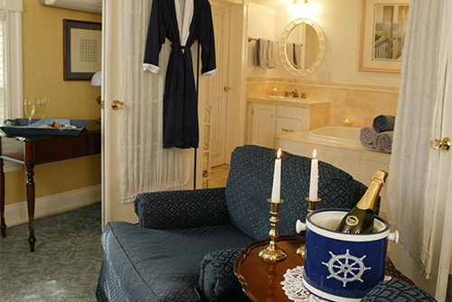Clarissa guest room with upholstered sitting chair, chilled Champagne and view of private bath with navy robe
