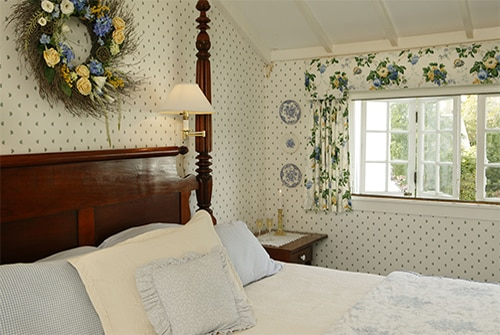 Clarissa Suite bedroom showing king bed with white linens and blue and yellow wallpaper