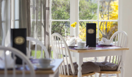 Table in the dining room showing setting for two and bud vase with yellow flowers