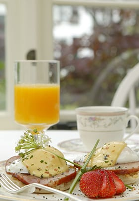 Breakfast entrée showing eggs Benedict with strawberry garnish and orange juice