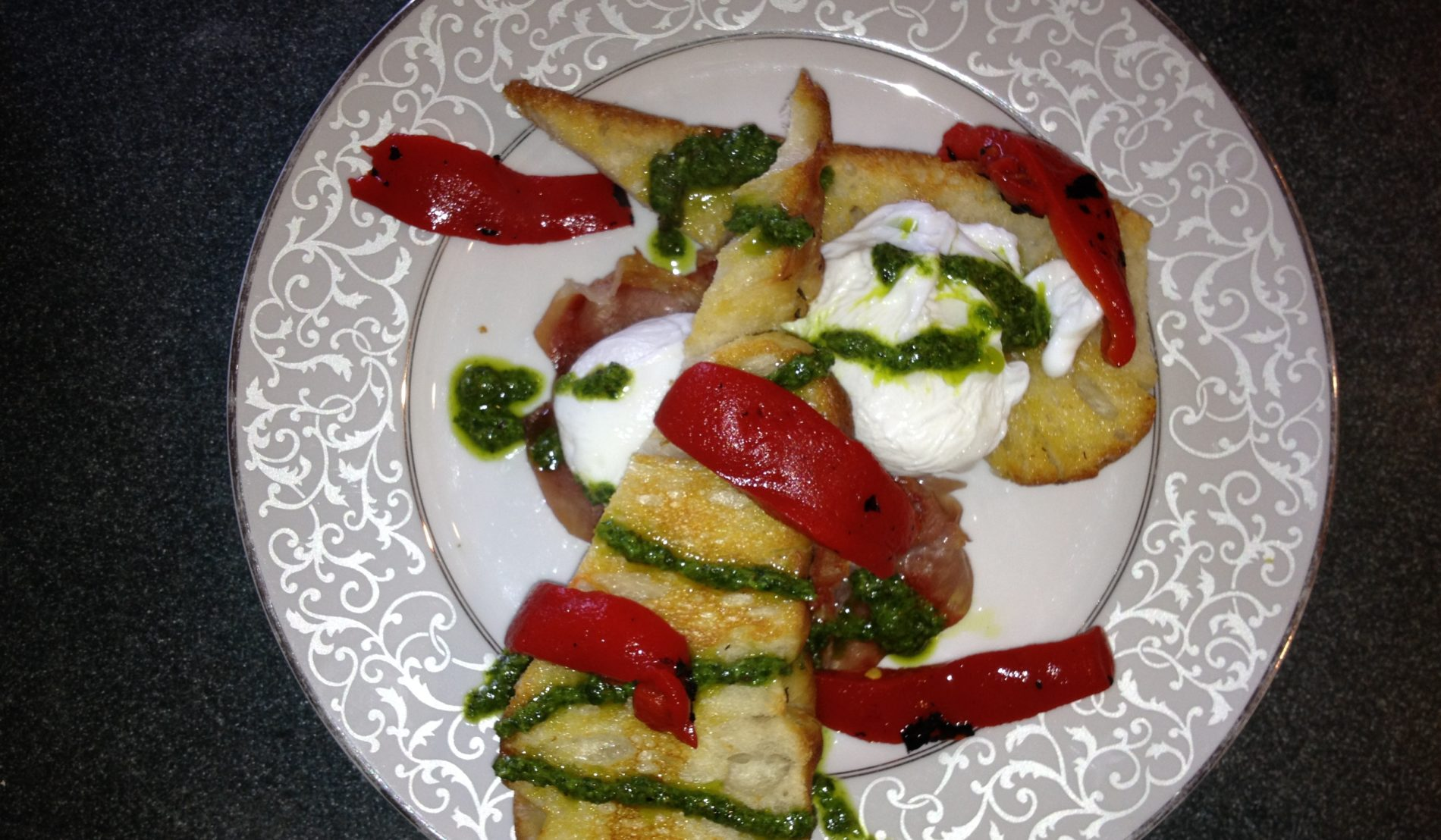 White scrolled plate topped with two slices of eggs Italiano, with red peppers, green sauce and sour cream
