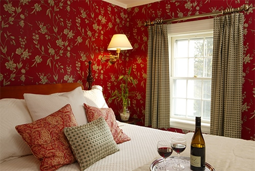 Eliza Jane Suite showing queen bedroom with deep red floral wallpaper and red wine