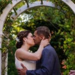 Bride and groom kissing under a white arched trellis with flowering vine
