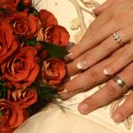 Groom and bride's hands with wedding rings alongside bouquet of red roses