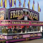 Large fried dough stand at a carnival selling funnel cakes, drinks and fried dough
