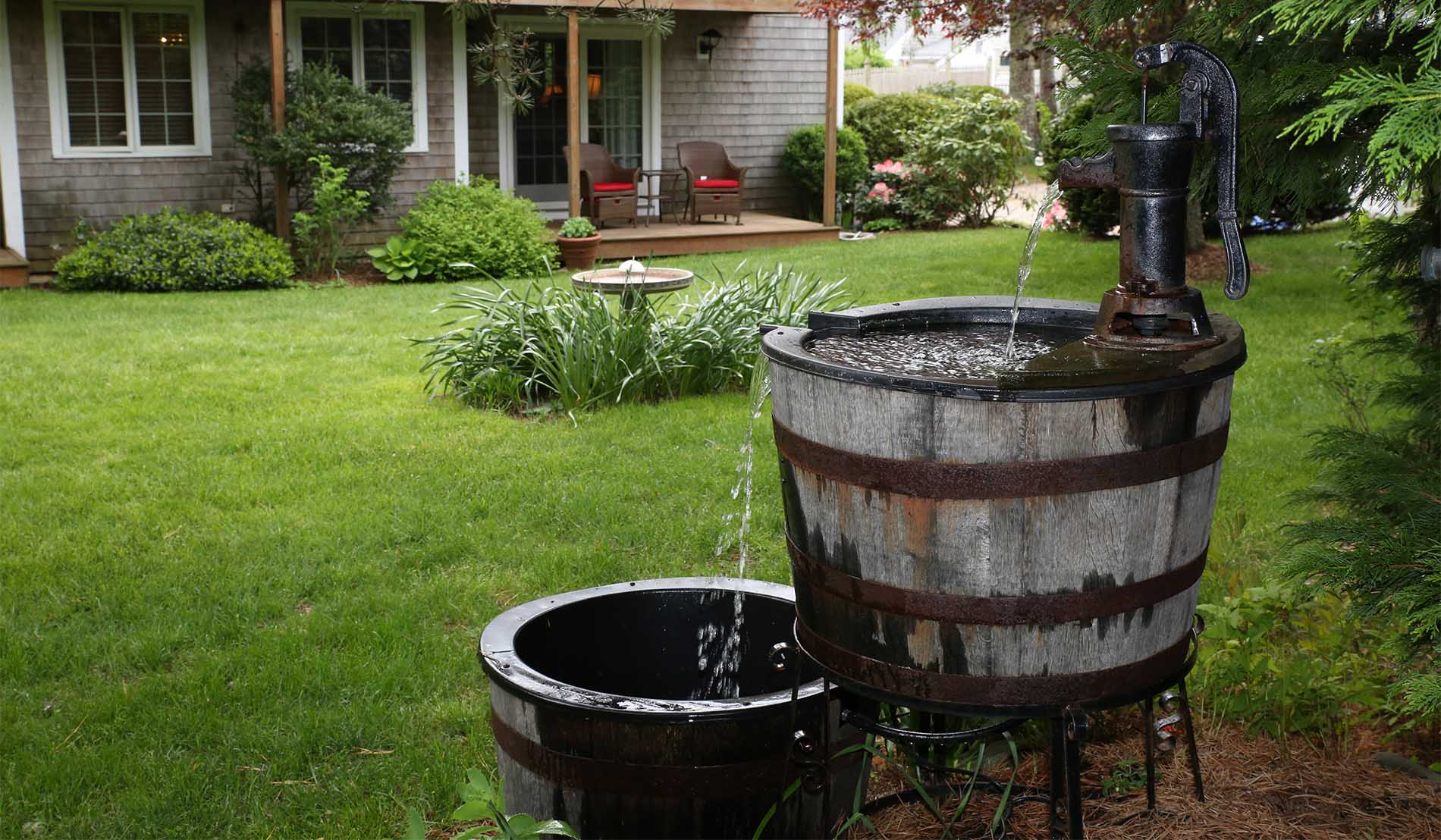 Double bucket fountain behind exterior of stables building showing guestroom patios in background