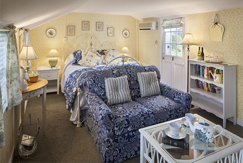 Garden room showing yellow, blue and white color scheme with queen bed and loveseat
