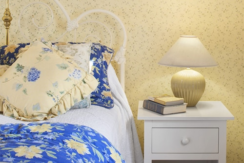 Garden guest room with white bed, blue and yellow bedding and white nightstand with yellow papered walls