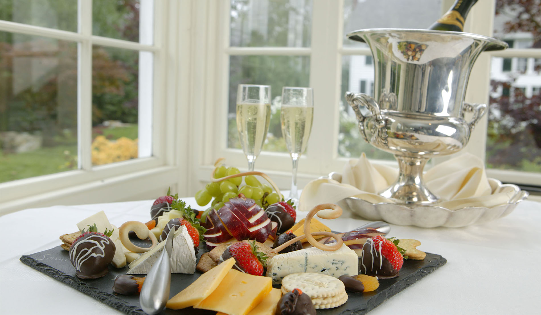 Romantic package in-room extra showing fruit, cheese, and chocolate dipped strawberry plate and champagne