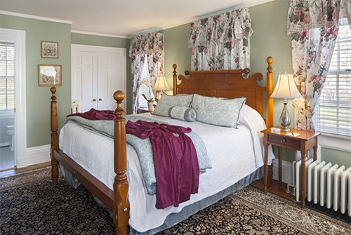 Hannah Rebekah guest room showing floral king bed and burgundy robes