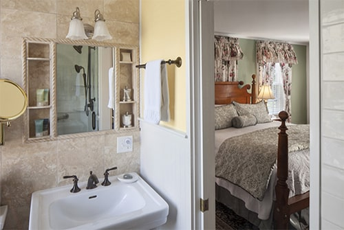 Hannah Rebekah pedestal sink in bathroom looking out to bedroom with floral king bed