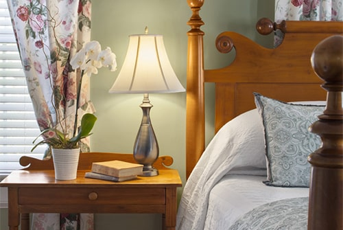 Hannah Rebekah guest room with wood bed and nightstand, windows with floral curtains