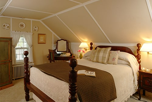 Hideaway Suite showing bedroom with queen bed and beige bedding, vanity area, and window with white curtains
