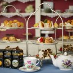 Three, 3-tiered dessert stands topped with lots of baked goodies and flowered teapot with cups and saucers