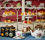 Three three-tiered dessert stands filled with snacks and a teapot with cups and saucers