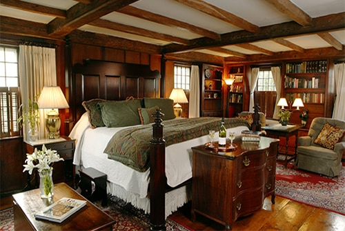 Hiram Harding guest room showing carved king bed with burgundy, gold, and deep green bedding and pumpkin wood paneled walls