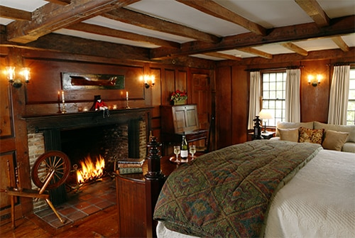 Hiram Harding Guest Room with paneled walls, fireplace, windows and quilted bed