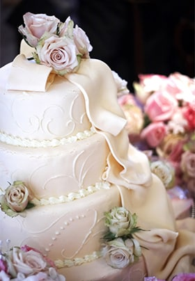 Beautiful four-tiered white wedding cake with pastel roses