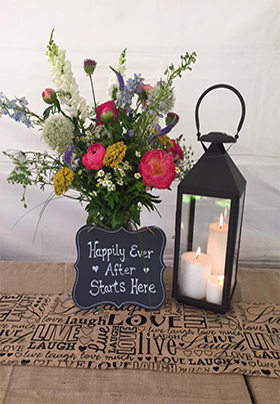 Table topped with fresh flowers, a lantern with lit candle and sign that reads: Happily Ever After Starts Here