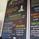 Chalkboard sign with colorful menu items at Arnold's Lobster & Clam bar in Eastham in Cape Cod