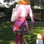 Female scarecrow in pink with a pumpkin head propped up in the grass