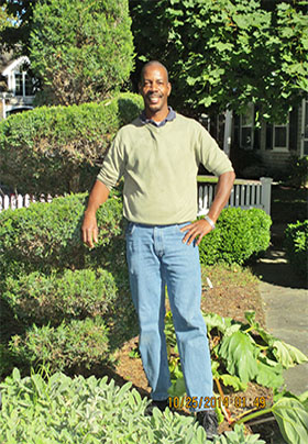 Smiling man standing outside next to manicured landscaping