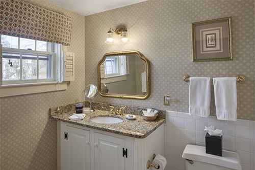 Intrepid bathroom showing marble vanity sink with brass fixtures and window with cornice