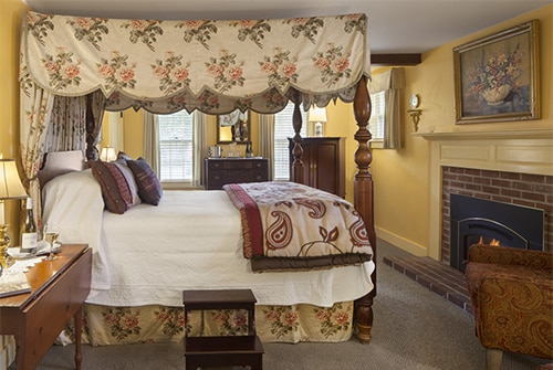 Intrepid guest room showing queen bed with floral and paisley bedding and fireplace