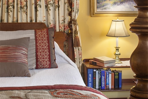 Intredpid guest room with wood bed, brown and red bedding, nightstand with lamp and books
