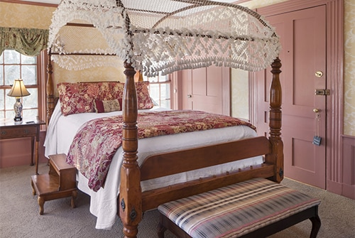 Lady Hope guest room showing queen canopy bed and decorative bench in pinks, yellows, and greens