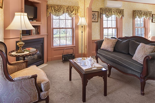 Lady Hope guest room with corner fireplace and TV, several windows and upholstered seating