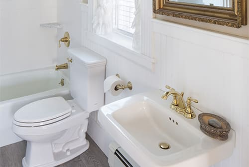 Lady Hope guest bath with tub, small window and white pedestal sink with gold mirror
