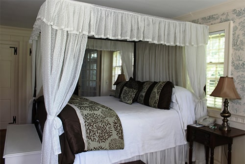Lady Mariah guest room showing king canopy bed with white bedding and sage green and brown duvet