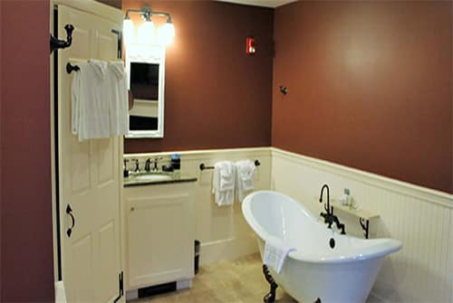 Lady Mariah bathroom showing deep red painted walls, marble vanity sink, and claw foot double soaking tub